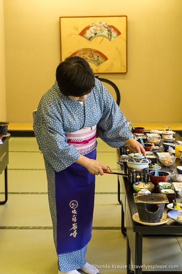 Woman in a yukata preparing a traditional Japanese dinner at a hot spring resort