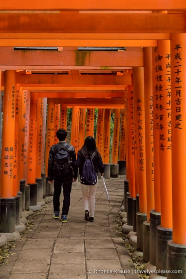 Young couple walking in the torii gate tunnel at Fushimi Inari shrine, Kyoto