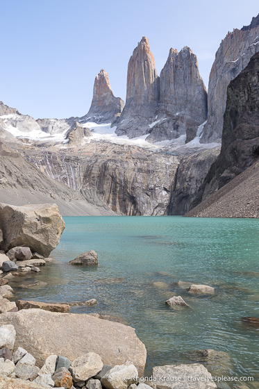The towers, Torres del Paine, overlooking a small turquoise lake.