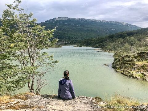Woman sitting on a small cliff looking at Lapataia River.