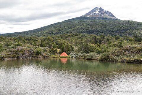 Tent on the shore of Ovando River with a mountain in the background.
