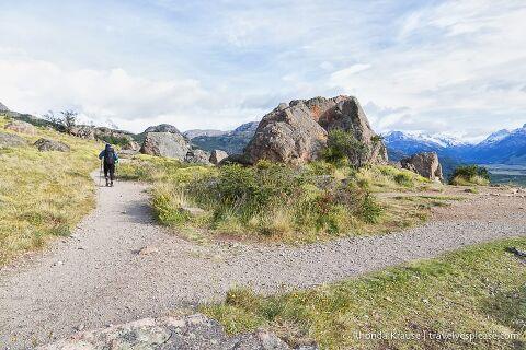 Hiker passing by a large rock at Mirador Rio de las Vueltas.