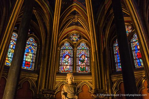 Statue and stained glass inside Sainte-Chapelle's lower chapel.
